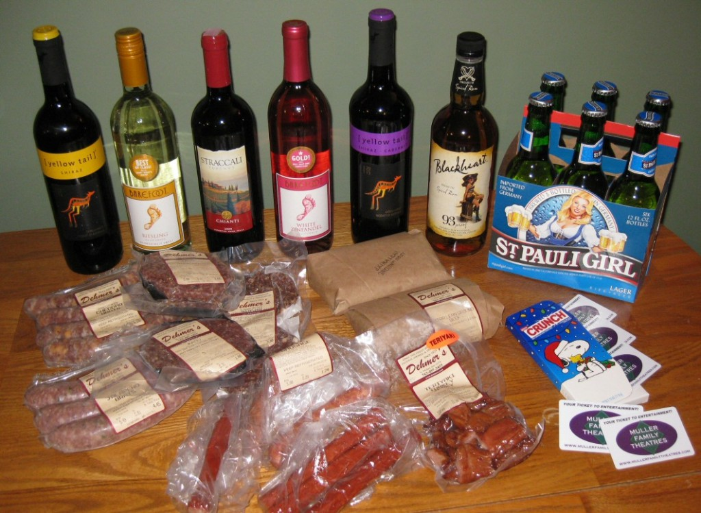 My 2014 Small Business Saturday haul: 5 bottles of wine, 1 bottle of rum, 6-pack of beer, some jerky and meat sticks, frozen brats and burgers, $50 in movie theater gift cards, and a kid's birthday gift (gift-wrapped, not pictured) ... all for about $11 in odd store totals.